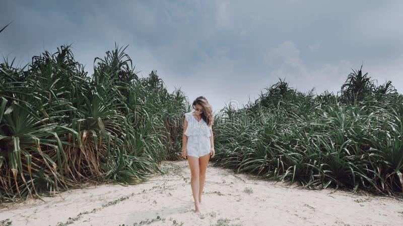 Flickan står mot bakgrunden av exotiska växter på stranden arkivfoto