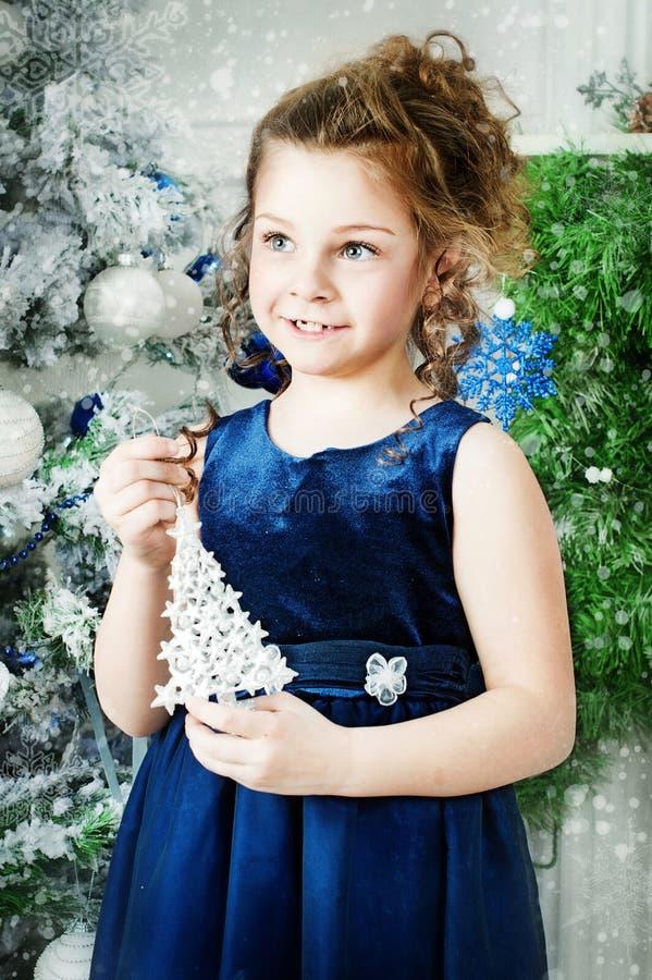 Flickan står nära julgranen royaltyfria bilder