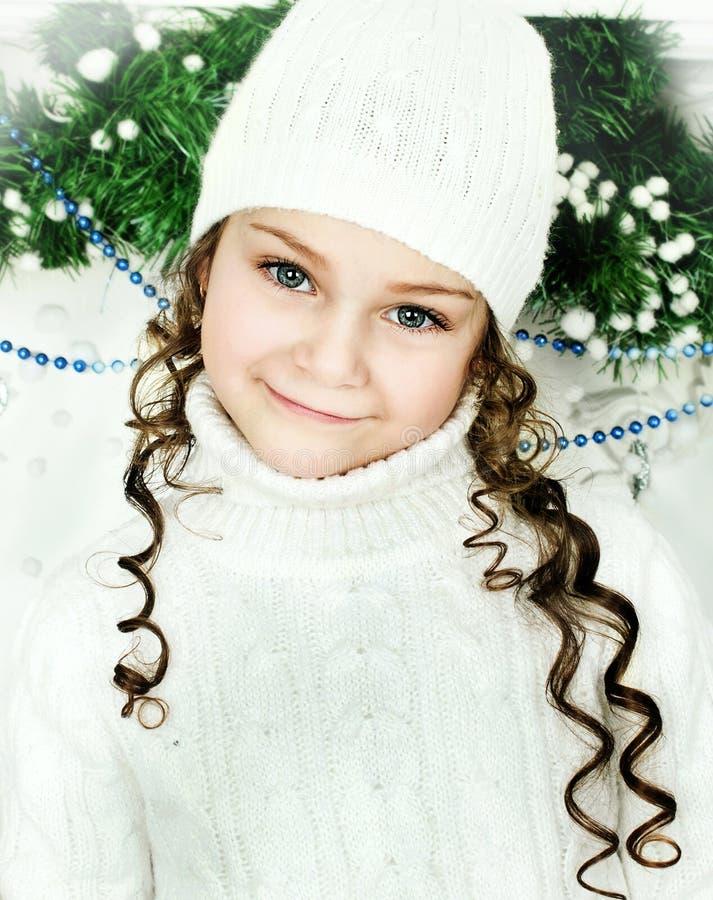 Flickan står nära julgranen royaltyfri foto
