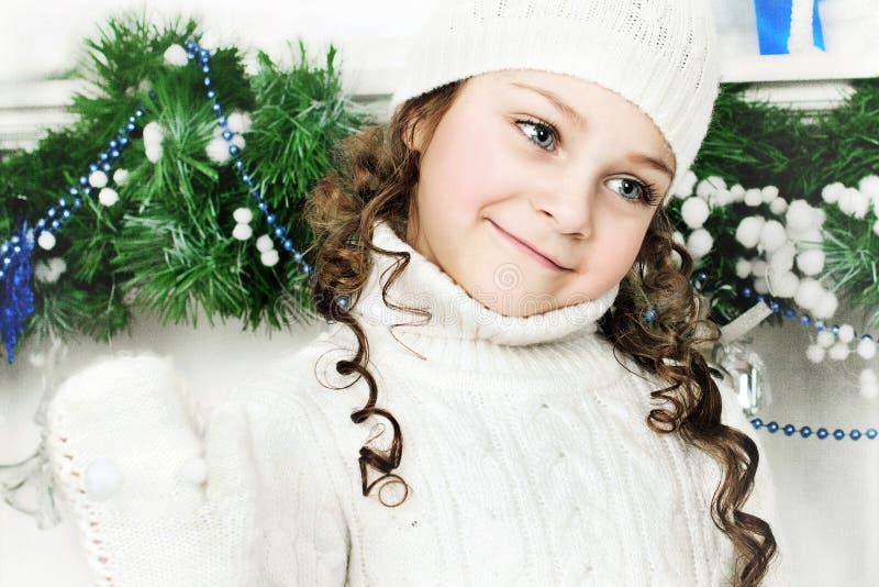 Flickan står nära julgranen arkivfoton