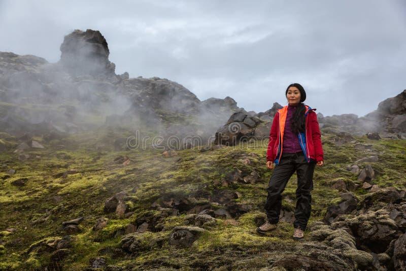 Flickan står på röka vaggar av Landmannalaugar i Island royaltyfria foton