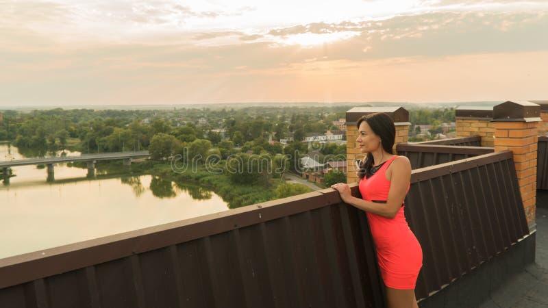 Flickan står på taket av ett hus wind för abstraktionstormsolnedgång arkivbild