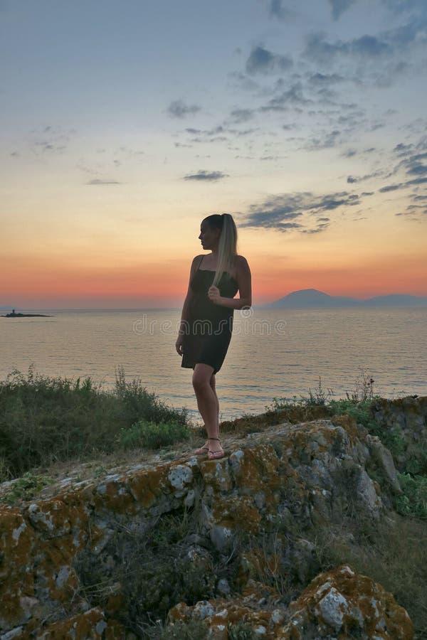 Flickan står på vaggar och blickar på den härliga sikten av havet och solnedgången arkivfoto