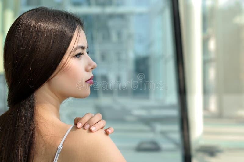 Flickan står tillbaka och ser bort royaltyfria foton