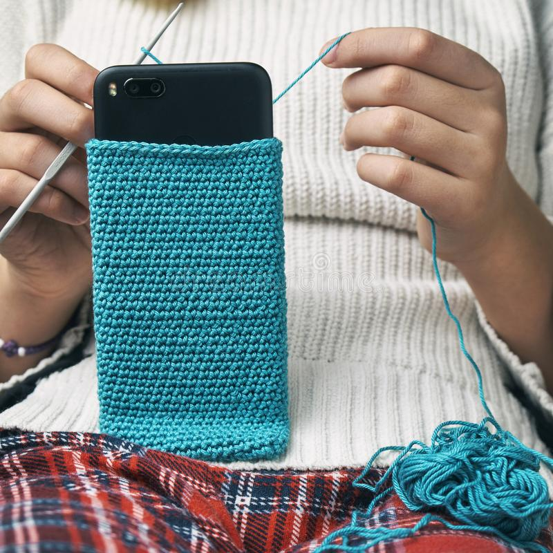 Flickan sticker ett woolen smartphonefall arkivfoto