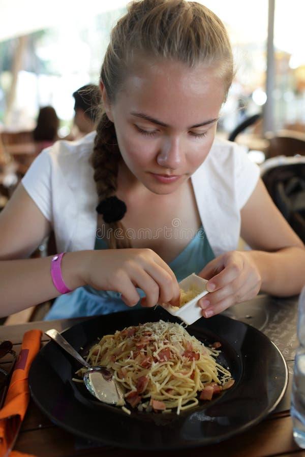 Flickan strilar spagetti med ost arkivbilder