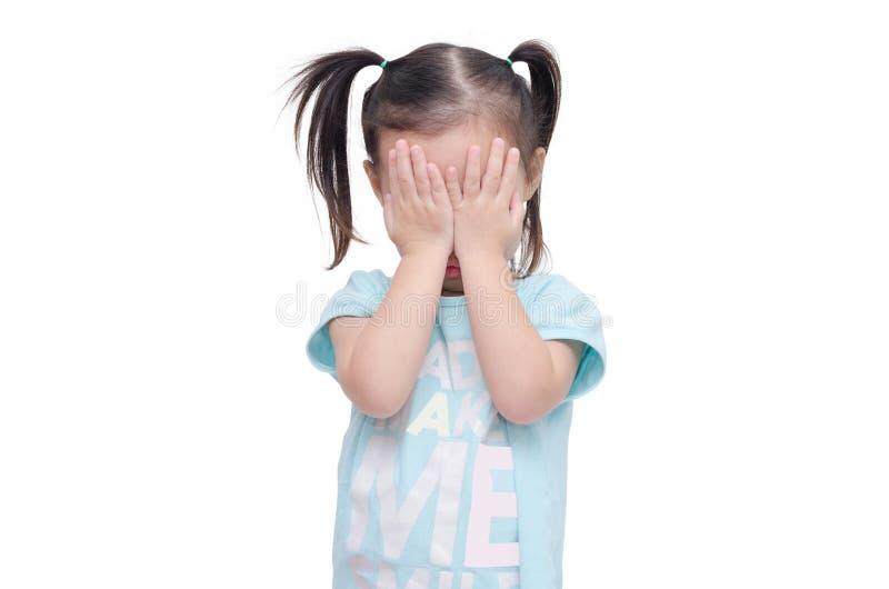 Flickan täcker hennes framsida vid händer över vit arkivfoton