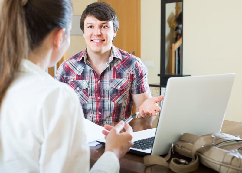 Flickan talar med mannen, medan intervjua honom hemma arkivfoton