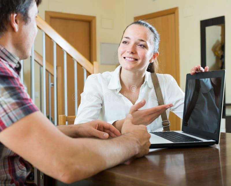 Flickan talar med mannen, medan intervjua honom hemma arkivbild