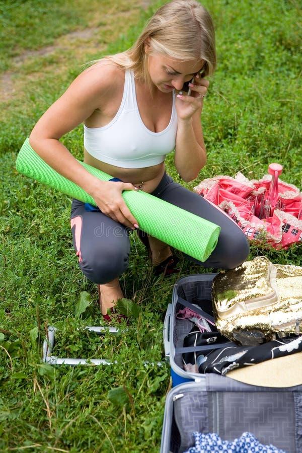 Flickan talar på telefonen bredvid en öppen resväska royaltyfria foton