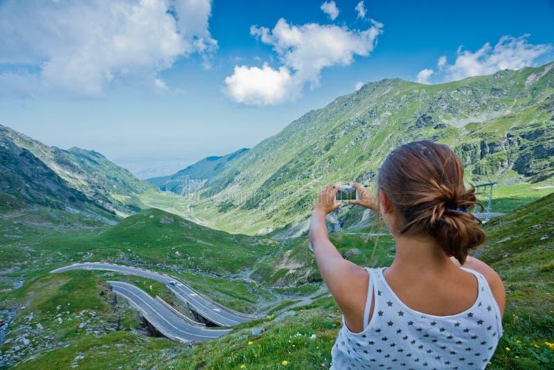 Flickan tar ett foto av den Transfagarasan bergvägen romania arkivfoto