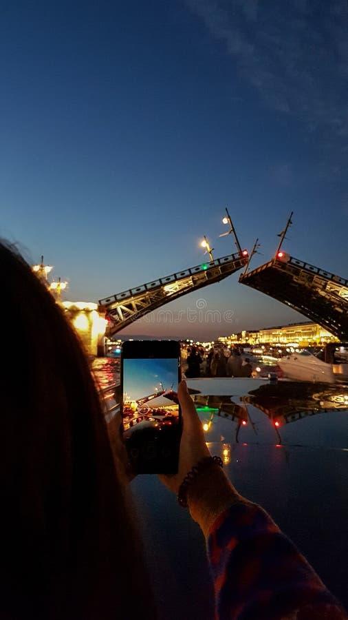 Flickan tar fotoet på bron för telefonavelslotten i St Petersburg under vita nätter Sikt från Neva River till den lyftta bron royaltyfria bilder