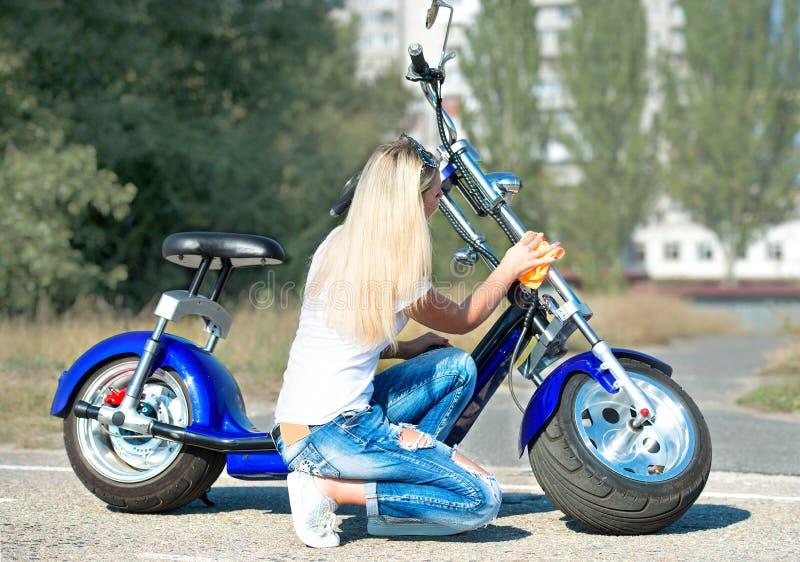 Flickan torkar hennes motorcykel med en trasa arkivfoton