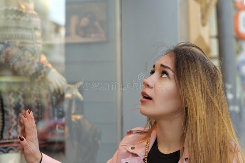Flickan trycker på det glass fallet av ett lager för kläder för kvinna` s royaltyfri fotografi