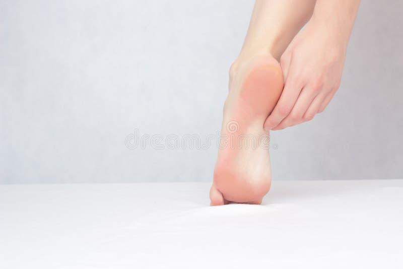 Flickan trycker på hans fot med hans fot och häl på en vit bakgrund, närbilden, kopieringsutrymme, dermatologi arkivfoto