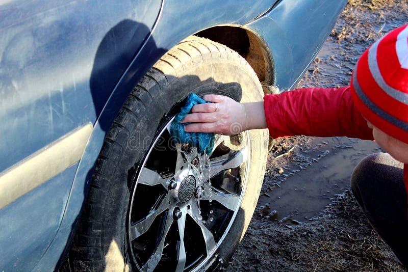 Flickan tvättar smutsen från hjulen av bilen arkivfoton