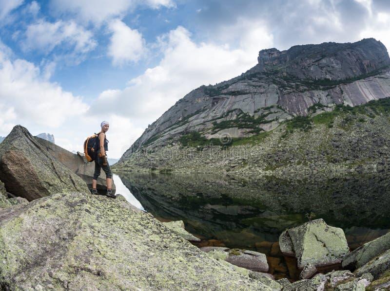 Flickan tycker om en härlig bergsjö, i den Ergaki nationalparken, Ryssland fotografering för bildbyråer