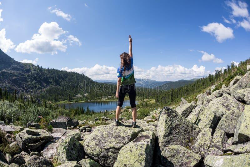 Flickan tycker om en härlig bergsjö, i den Ergaki nationalparken, Ryssland arkivbilder