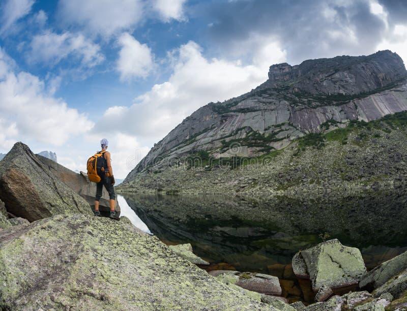 Flickan tycker om en härlig bergsjö, i den Ergaki nationalparken, Ryssland royaltyfri bild