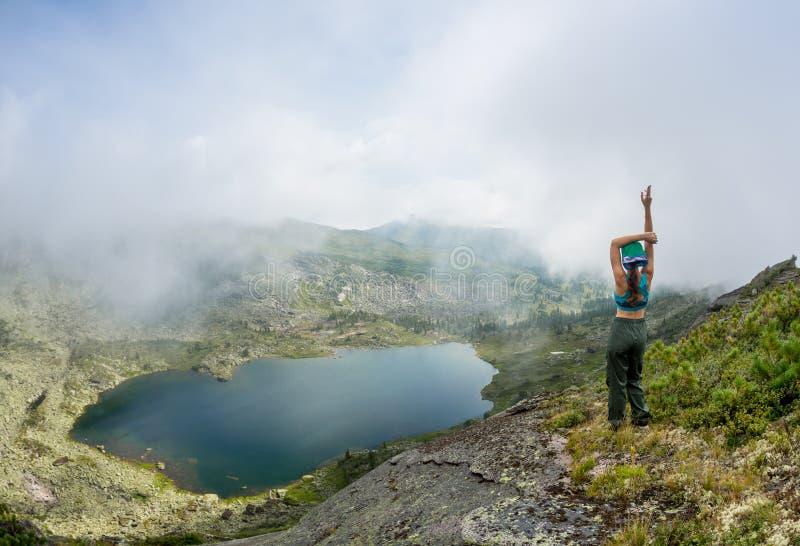 Flickan tycker om en härlig bergsjö, i den Ergaki nationalparken, Ryssland royaltyfria foton