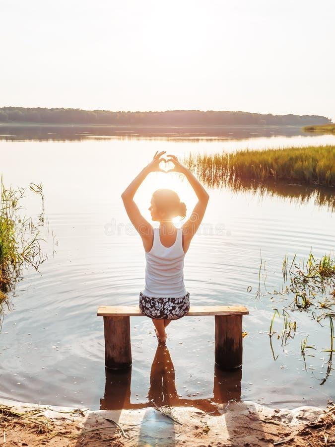 Flickan tycker om en härlig solnedgång sitter på en bänk vid floden, och showhänder fingrar hjärtatecknet Flicka som nära sitter royaltyfria bilder