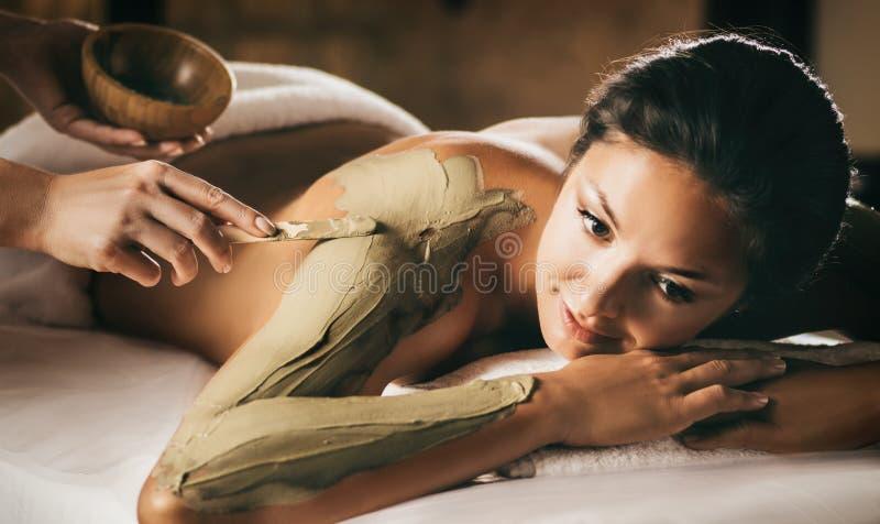 Flickan tycker om gyttjakroppmaskeringen i en brunnsortsalong Fokus på handen med pinnen arkivbild