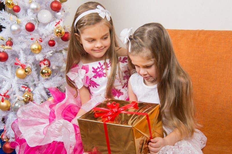 Flickan uppmuntrar en annan flicka som gav den fel gåvan royaltyfria bilder