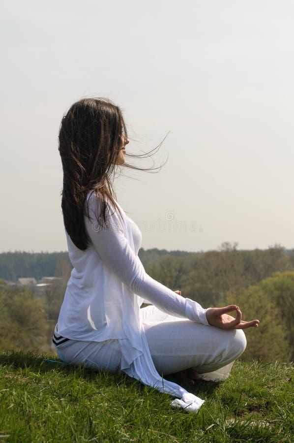 Flickan utför yoga på kullen mot den blåa himlen arkivbilder