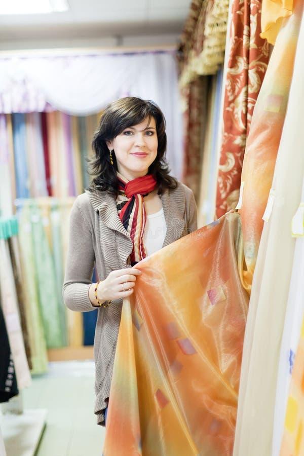 Flickan väljer gardiner arkivfoton