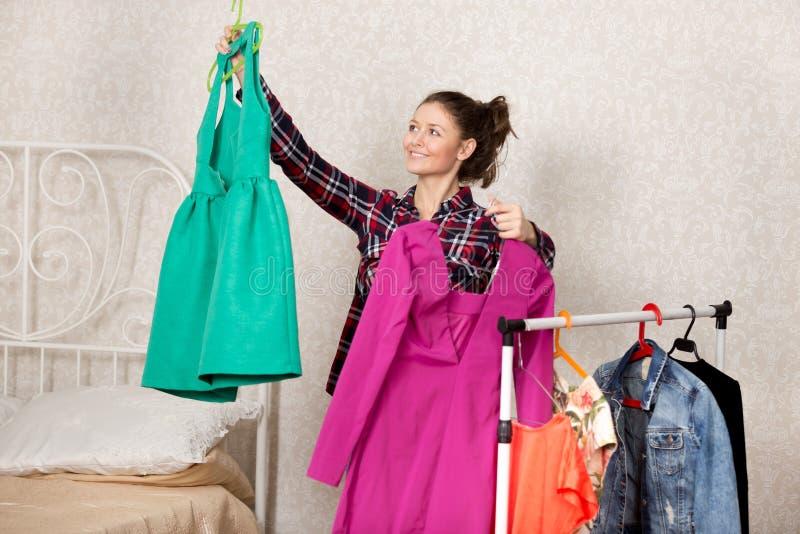Flickan väljer klänningar fotografering för bildbyråer