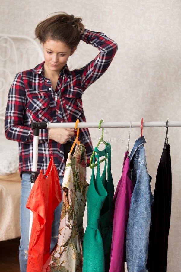 Flickan väljer klänningar arkivfoton