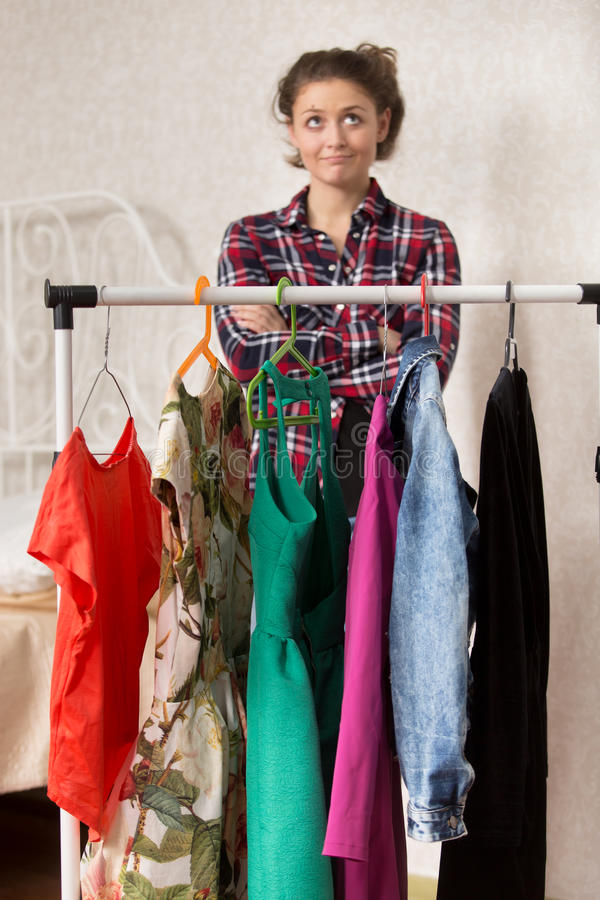 Flickan väljer klänningar royaltyfri foto