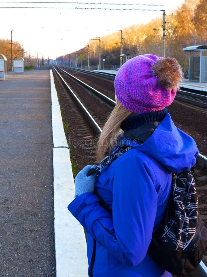 Flickan väntar på drevet som ser järnvägsspåren Hösttema av kläder och väder royaltyfria foton