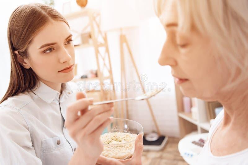 Flickan vårdar den äldre kvinnan hemma Flickan hjälper kvinnan med mat royaltyfri bild