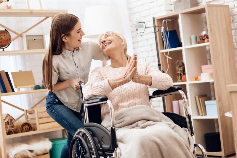 Flickan vårdar den äldre kvinnan hemma Flickan rider kvinnan i rullstol Kvinnan tycker sig om fotografering för bildbyråer