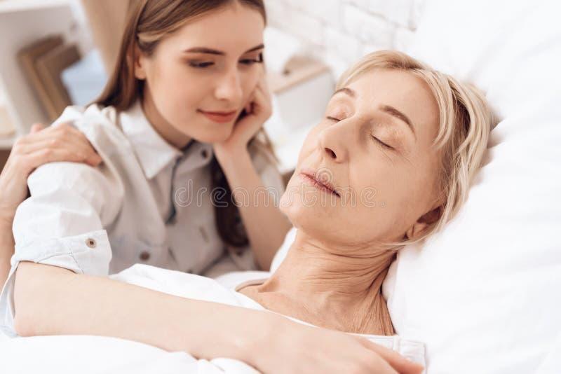 Flickan vårdar den äldre kvinnan hemma Kvinnan sover fridfullt arkivfoton
