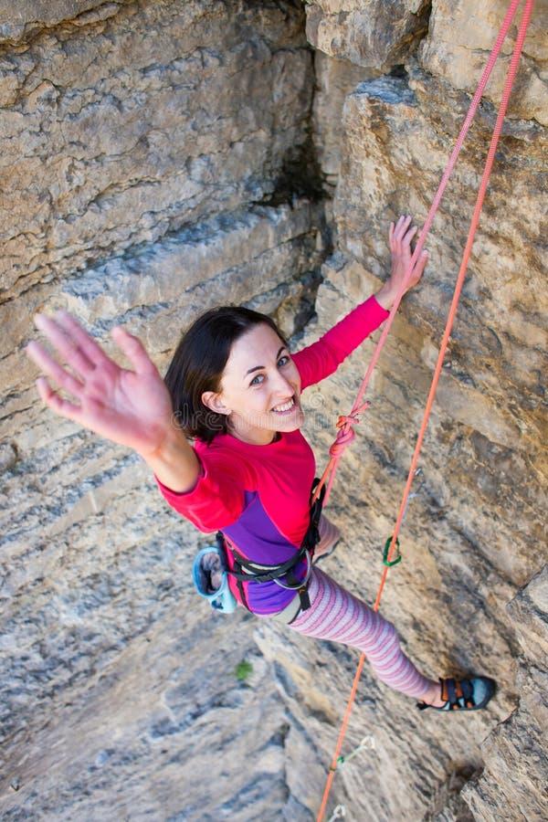 Flickan vaggar klättraren har nått överkanten av klippan royaltyfria bilder
