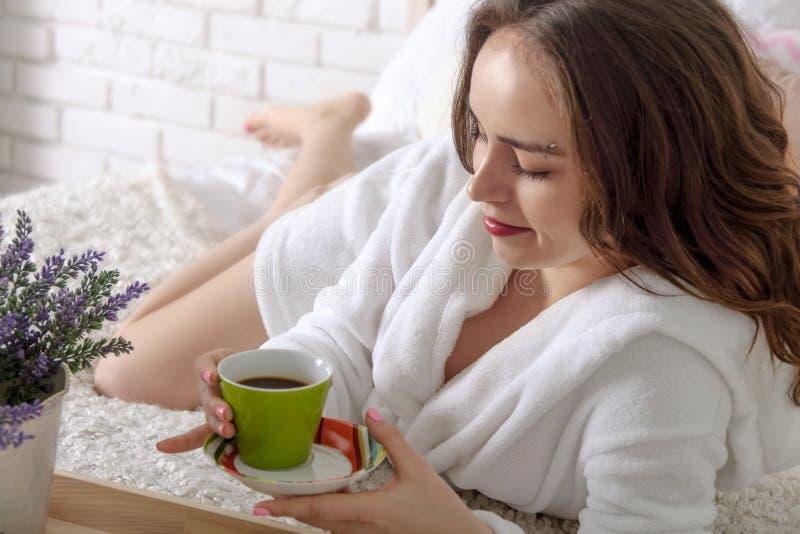 Flickan vaknade upp i morgon- och drinkkaffet royaltyfri fotografi