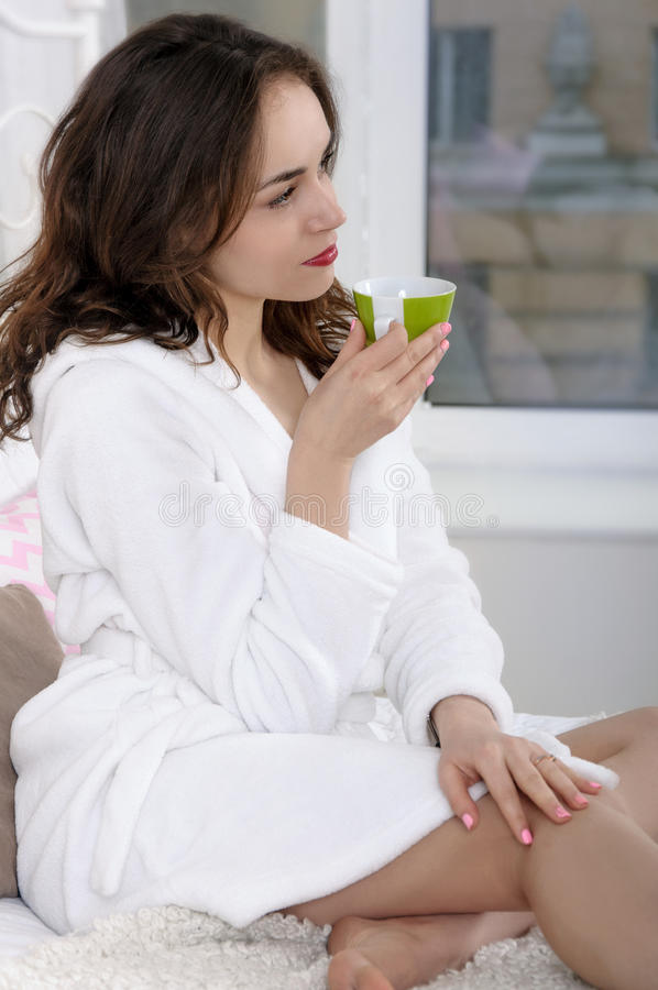 Flickan vaknade upp i morgon- och drinkkaffet royaltyfri bild