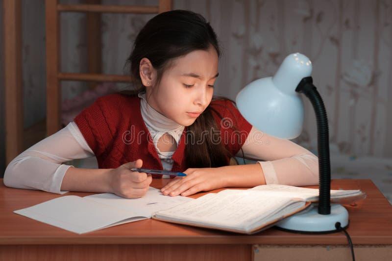 Flickan var mycket trött att göra läxa fotografering för bildbyråer