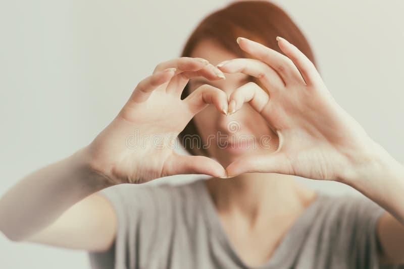 Flickan visar konturn av hjärta av fingret arkivbild