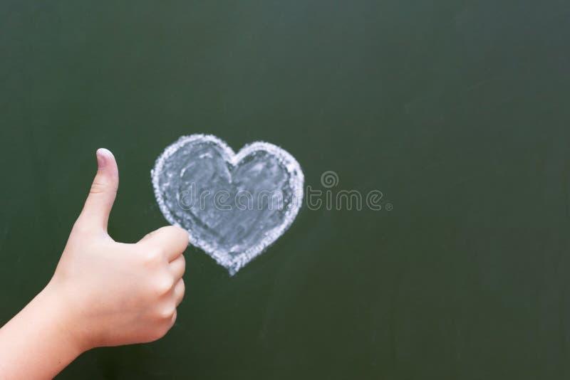 Flickan visar vid handen som är ok bredvid hjärtan som dras av kritan på en svart tavla Lyckönskan på dag för valentin` s Fritt u royaltyfria foton