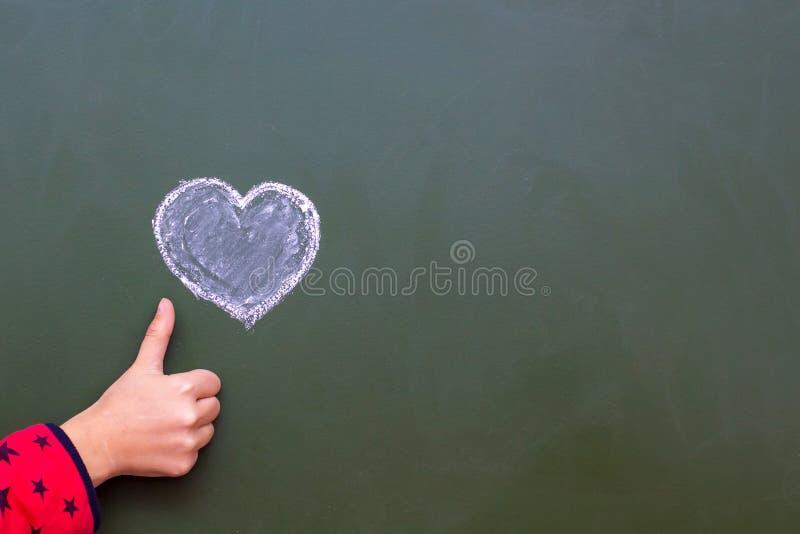 Flickan visar vid handen som är ok bredvid hjärtan som dras av kritan på en svart tavla Lyckönskan på dag för valentin` s Fritt u arkivfoton
