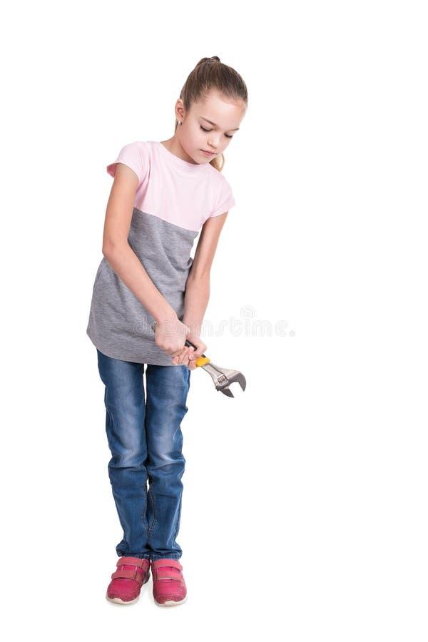 Flickan vrider den justerbara skiftnyckeln royaltyfri bild