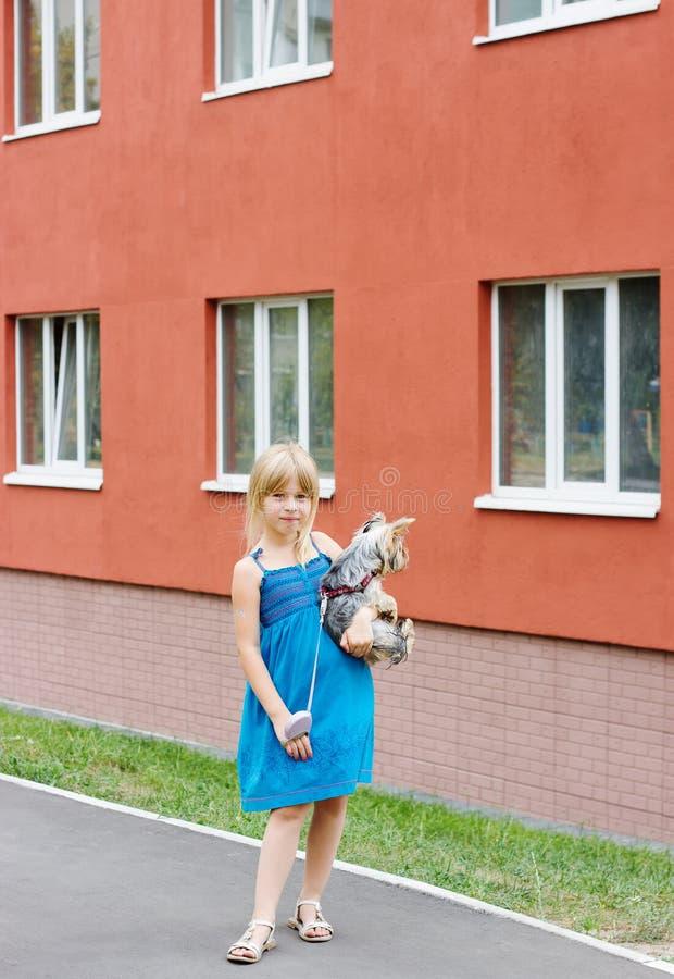 Flickan 5years med den Yorkshire terriern i henne armar near höghus royaltyfri fotografi