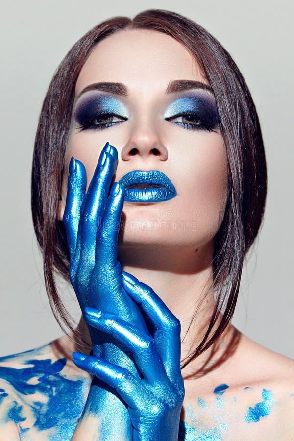 Flickans framsida med blå makeup royaltyfria foton