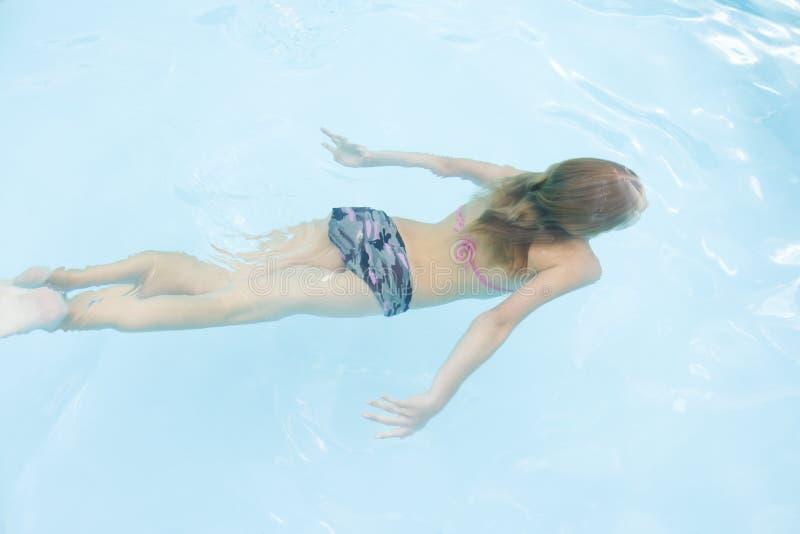 flickapöl som simmar undervattens- barn arkivfoto
