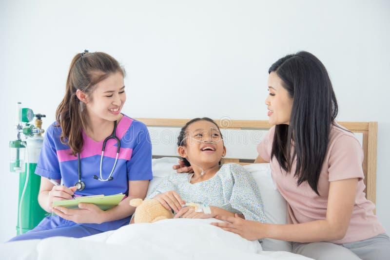 Flickapatient och moder som ler stunddoktorn arkivfoto