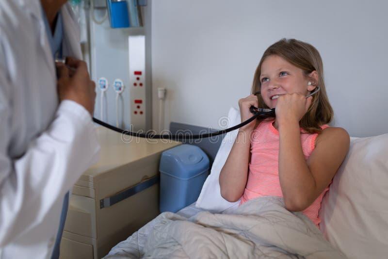 Flickapatient som lyssnar till doktorshjärtatakten med stetoskopet arkivfoto