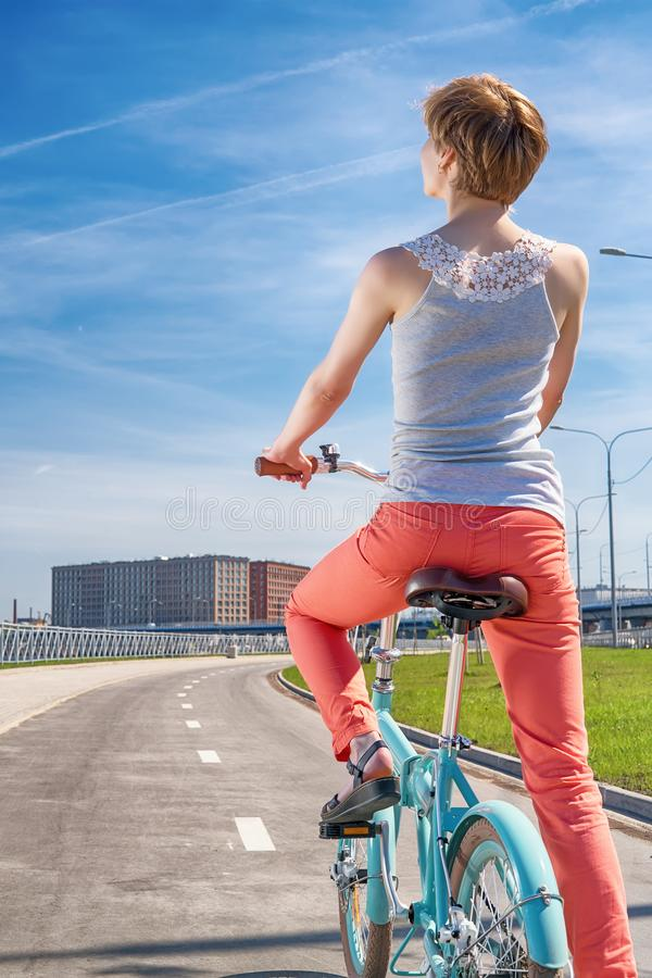 Flickaridning på den blåa vikningcykeln som ser ljus cityscape arkivbilder